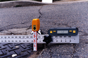 Measuring equipment showing hole depth in roadway